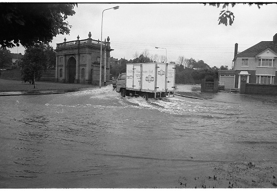 "Flooding at the Dodder..1986..26.08.1986..08.26.1986..28th August 1986..As a result of Hurricane Charly (Charlie) heavy overnight rainfall was the cause of severe flooding in the Donnybrook/Ballsbridge areas of Dublin. In a period of just 12 hours it was stated that 8 inches of rain had fallen. The Dodder,long regarded as a ""Flashy"" river, burst its banks and caused great hardship to families in the 300 or so homes which were flooded. Council workers and the Fire Brigades did their best to try and alleviate some of the problems by removing debris and pumping out some of the homes affected..Note: ""Flashy"" is a term given to a river which is prone to flooding as a result of heavy or sustained rainfall...Vans and trucks cause a small tidal wave as they negotiate the flood waters."