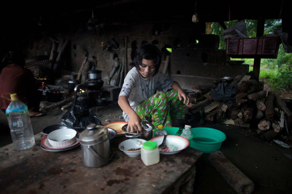 Nmau Hkawn Htoija, from Shadanpa village and 14 years old, cook up the breakfast for her family in Woi Chyai Internal Displacement People refugee camp in Laiza village close to the China border, Myanmar on July 16, 2012. According to KIO (Kachin Independence Organization) sources around 50000 Kachin people live as refugees in those camps.