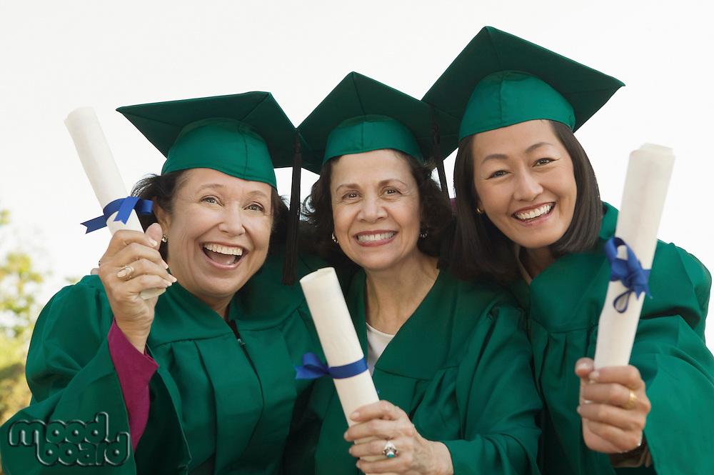 Smiling Graduates Holding Their Degrees