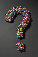 Various pills forming question mark on black background