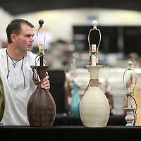 Shane Mann, with the H & H Lamp Company of Rutherford Tennessee, places a variety of lamps out for display as he sets up the show space in building VI for the upcoming winter Tupelo Furniture Market that starts on Thursday.