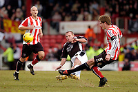 Photo: Leigh Quinnell.<br /> Brentford v Swansea City. Coca Cola League 1.<br /> 26/12/2005. Swanseas Andy Robinson challenges Brentfords Michael Turner. A challenge which earned Andy Robinson a yellow card.