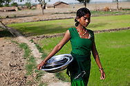 Pramila Tharu, 15, does household chores in Bhaishahi village, Bardia, Western Nepal, on 29th June 2012. Pramila eloped and married at 12 and gave birth to Prapti at age 13. She delivered prematurely on the way to the hospital in an ox cart and her baby weighed only 1.5kg at birth. In Bardia, StC works with the district health office to build the capacity of female community health workers who are on the frontline of health service provision like ante-natal and post-natal care, especially in rural areas. Photo by Suzanne Lee for Save The Children UK
