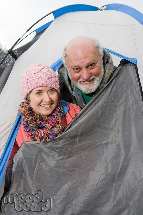 Senior couple in entrance to tent, portrait