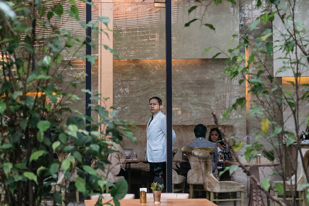 A waiter watches the door at Myron's Place, one of several upscale restaurants at the Greenbelt Mall in Makati City, Manila, Philippines.
