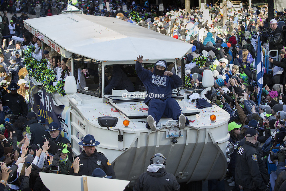 Marshawn Lynch throws Skittles to the crowd at a huge downtown parade celebrating the Seahawks' first Super Bowl title.<br />