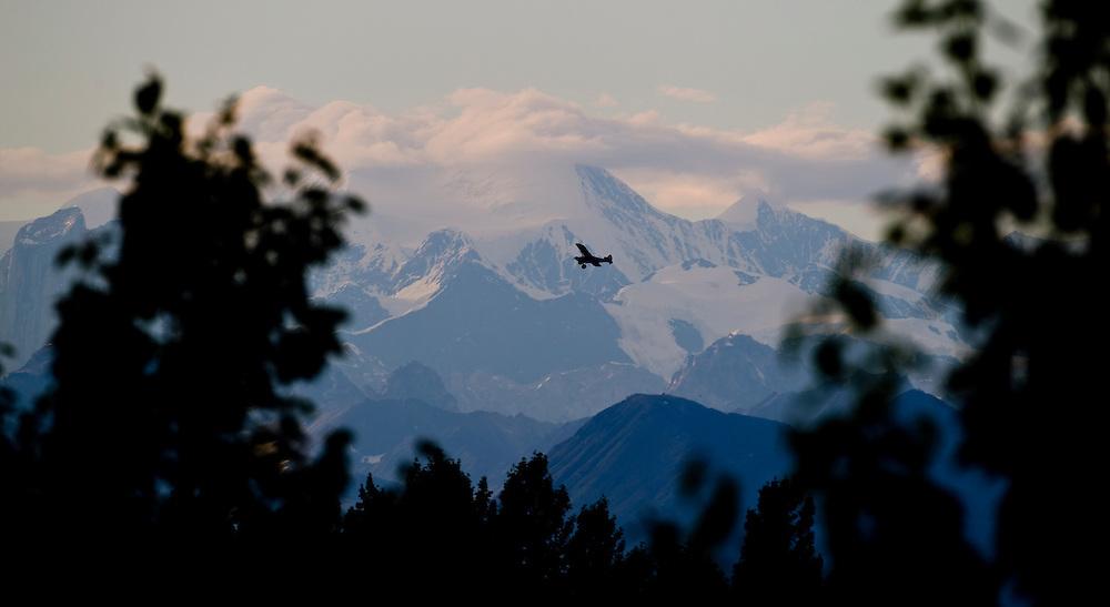 Alaska2010.-A bush plane flies around Denali the largest mountain in North America located in Denali National Park Alaska.