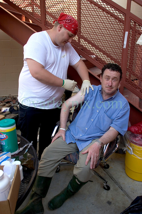08 Sept 2005. New Orleans, Louisiana. Hurricane Katrina aftermath.<br /> The Daily Mirror's Aidan McGurran gets his hepatitis A and B and tetanus shots from paramedic  Ken Janik from Cleveland, Ohio at a makeshift clinic at the 2nd precinct in uptown New Orleans.<br /> Photo; &copy;Charlie Varley/varleypix.com