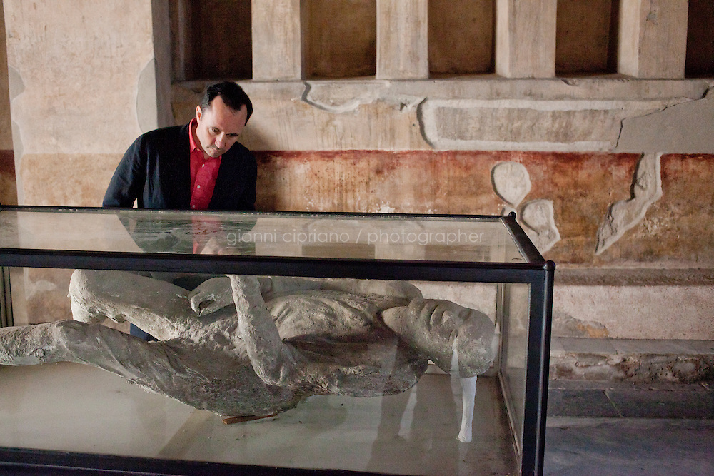 POMPEII, ITALY - 4 APRIL 2013: A tourist observes a plaster body cast shown in the Stabian Baths, in Pompeii, Italy, on April 4th, 2013. During the eruption of Mount Vesuviusin 79 AD, the ash lithified before the corpses decayed so that a good mold of the deceased remained. Early in the excavation it was discovered that filling these molds with plaster produced remarkable casts of the victims of the eruption. ..In recent years, a series of collapses at the site have alarmed conservationists, who warn that the ancient Roman city is dangerously exposed to the elements ? and poorly served by the red tape, lack of strategic planning and limited personnel of the site's historically troubled management. ..Pompeii, along with Herculaneum, was buried under 4 to 6 meters (13 to 20 ft) of ash and pumice in the eruption of Mount Vesuvius in 79 AD. After its initial discovery in 1599, Pompeii was rediscovered as the result of intentional excavations in 1748 by the Spanish military engineer Rocque Joaquin de Alcubierre...Pompeii is an UNESCO World Heritage Site and one of the most popular tourist attractions of Italy, with approximately 2.5 million visitors every year...Gianni Cipriano for The New York Times