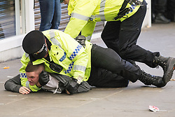 © Licensed to London News Pictures . 13/05/2013 . Manchester , UK . Police pin a man to the ground opposite the City Store after fans and police scuffled when police attempted to push Manchester United fans up Market Street , away from the City Store . Police confront 100s of Manchester United fans outside the Manchester City store on Market Street after the Manchester United victory parade , this evening (13th May 2013) Photo credit : Joel Goodman/LNP