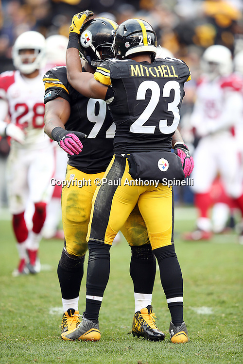 Pittsburgh Steelers outside linebacker James Harrison (92) gets a pat on the helmet in celebration from Pittsburgh Steelers free safety Mike Mitchell (23) after Harrison sacks Arizona Cardinals quarterback Carson Palmer (3) for a third quarter loss of 7 yards during the 2015 NFL week 6 regular season football game against the Arizona Cardinals on Sunday, Oct. 18, 2015 in Pittsburgh. The Steelers won the game 25-13. (©Paul Anthony Spinelli)