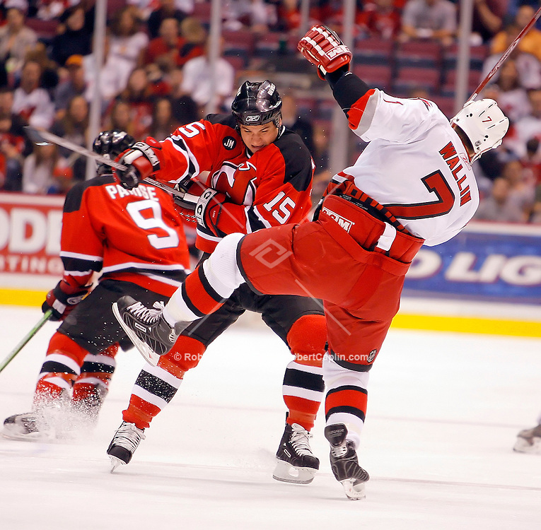 New Jersey's Jamie Langenbrunner checks Carolina's Niclas Wallin during the 1st period of the Carolina Hurricanes vs New Jersey Devils match-up at the Meadowlands May 13, 2006. Robert Caplin For The New York Times