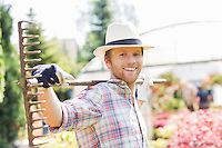 Portrait of smiling gardener carrying rake on shoulders at plant nursery