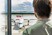 Rear view of man looking at the airplane through the window in airport