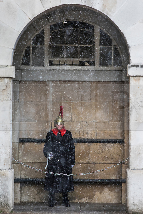 © Licensed to London News Pictures. 26/02/2018. London, UK. A member of the Household Cavalry Regiment on guard as snow falls on Whitehall. Severe cold, blizzards and heavy snow are expected as the 'Beast from the East' brings freezing Siberian air to the UK. Photo credit: Rob Pinney/LNP