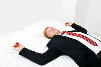 Mid adult businessman sleeping in bed at home