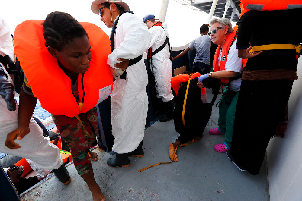 Migrants are helped to board the Migrant Offshore Aid Station (MOAS) ship MV Phoenix some 20 miles (32 kilometres) off the coast of Libya, August 3, 2015.  118 migrants were rescued from a rubber dinghy off Libya on Monday morning . The Phoenix, manned by personnel from international non-governmental organisations Medecins san Frontiere (MSF) and MOAS, is the first privately funded vessel to operate in the Mediterranean.<br /> REUTERS/Darrin Zammit Lupi <br /> MALTA OUT. NO COMMERCIAL OR EDITORIAL SALES IN MALTA