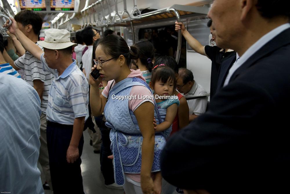 Woman on the phone in the Seoul metro, South Korea. 2009