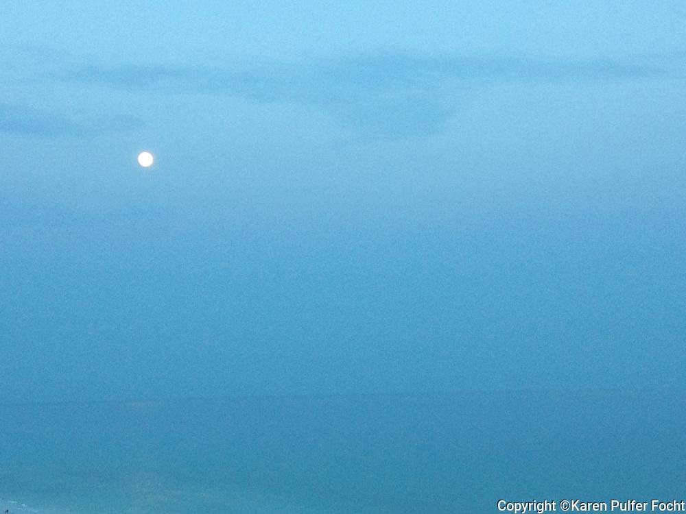 A blue ocean scene with a moon rise.
