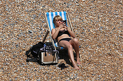 © Licensed to London News Pictures.21/06/2014. Brighton, UK. A woman sunbathing on Brighton Beach. Thousands of people are taking a weekend away to the South Coast with temperatures reaching 25C. Photo credit : Hugo Michiels/LNP