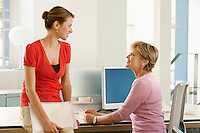Two female office workers talking at cubicle