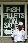 A man stands next to a sign offering fish fillets for sale at the Fishing Village.
