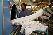 Unloading sheets from a dryer in the laundry room. HMP Coldingley, Surrey was built in 1969 and is a Category C training prison. Coldingley is focused on the resettlement of prisoners and all prisoners must work a full working week within the prison. Its capacity is 390 prisoners.