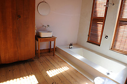 Cape Town - 180709 - Star Homes - 3 Regeant Road, Woodstock. He is a world renowned bronze sculptor and lives in Woodstock. Ferdi Dick is a world renowned bronze sculptor and lives in Woodstock. In oic is the bathroom with sunken bath and wardrobe -   photographer - Tracey Adams/African News