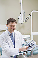 Dentist leafing through medical record