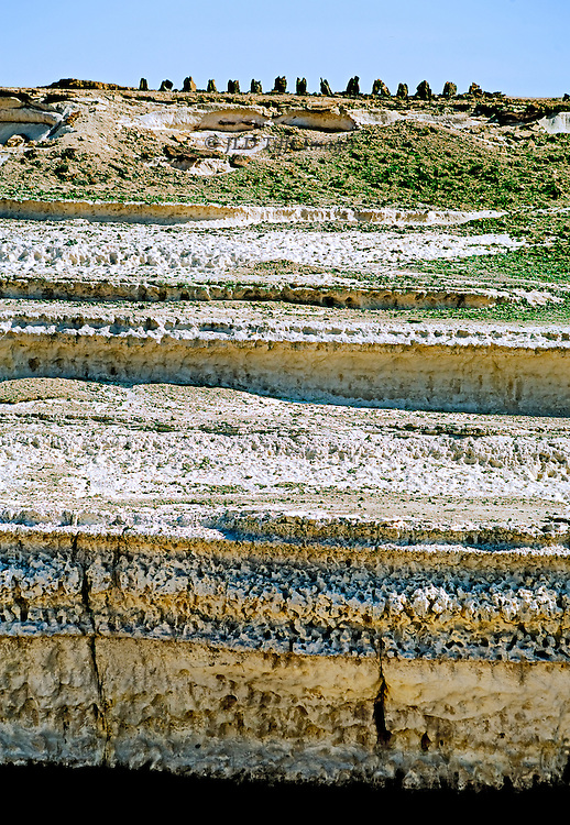 "Cliff formations in the vast Wadi Haynun, near the UNESCO ""Land of Frankincense"" preservation area, Dhofar, Oman.  Multiple horizontal striations in blues, yellows, and white, interspersed with white and beige sand.  Pale blue sky above."