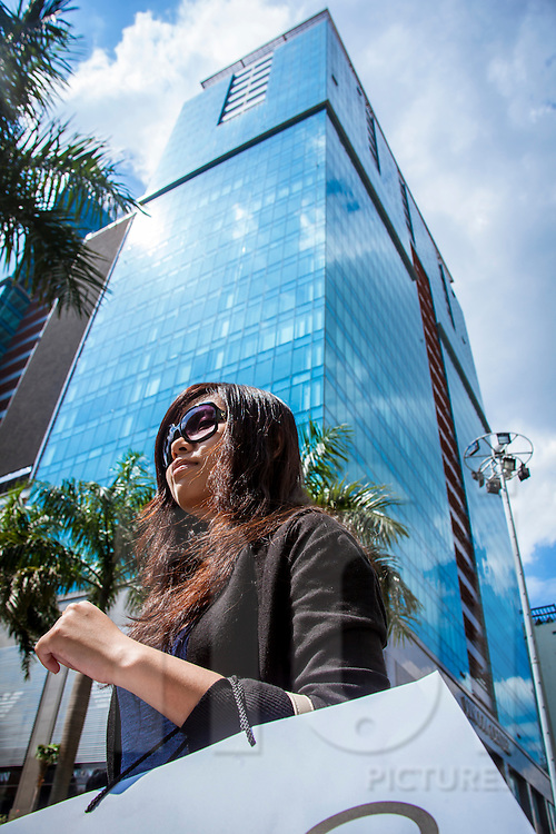 Below view of a vietnamese woman walking in front  of Vincom center. Ho Chi Minh city, Vietnam, Asia
