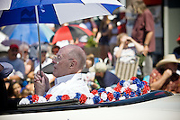 JEROME A. POLLOS/Press..Parade grand marshall Ace Walden protects himself with an umbrella from the hot sun while sitting in the back of a convertible.