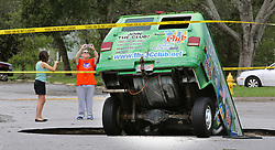 Residents take photos of a van remaining in a sinkhole on Monday, September 11, 2017, that opened up at the Astor Park apartment complex in Winter Springs, FL, USA, during Hurricane Irma's passing through central Florida Sunday night. The glass on the ground is the window that the driver punched out to extract himself after driving into the sinkhole. Photo by Joe Burbank/Orlando Sentinel/TNS/ABACAPRESS.COM