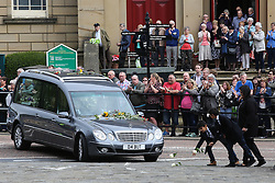 © Licensed to London News Pictures. 15/07/2016. Batley, UK. A family puts down flowers in front of Jo Cox's funeral cortege as it passes through her hometown of Batley, West Yorkshire. The Labour MP was stabbed and shot in the street as she left her constituency surgery last month. Thomas Mair was arrested in connection with the murder and is set to face trial this year.  Photo credit : Ian Hinchliffe/LNP