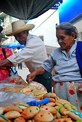 "MEXICO, Veracruz, Tantoyuca, Oct 27- Nov 4, 2009. Man and wife shop for ""pan muerto"" offerings in Tantoyuca. ""Xantolo,"" the Nahuatl word for ""Santos,"" or holy, marks a week-long period during which the whole Huasteca region of northern Veracruz state prepares for ""Dia de los Muertos,"" the Day of the Dead. For children on the nights of October 31st and adults on November 1st, there is costumed dancing in the streets, and a carnival atmosphere, while Mexican families also honor the yearly return of the souls of their relatives at home and in the graveyards, with flower-bedecked altars and the foods their loved ones preferred in life. Photographs for HOY by Jay Dunn."