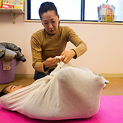 "TOKYO, JAPAN - JANUARY 29 : A woman wrapping participant during a workshop called ""Otonamaki"", which directly translates to adult wrapping, in Tokyo, Japan on Sunday, January 29, 2017. Otonamaki is a Japanese therapeutic method meant to alleviate posture problems and stiffness. (Photo by Richard Atrero de Guzman/ANADOLU Agency)"