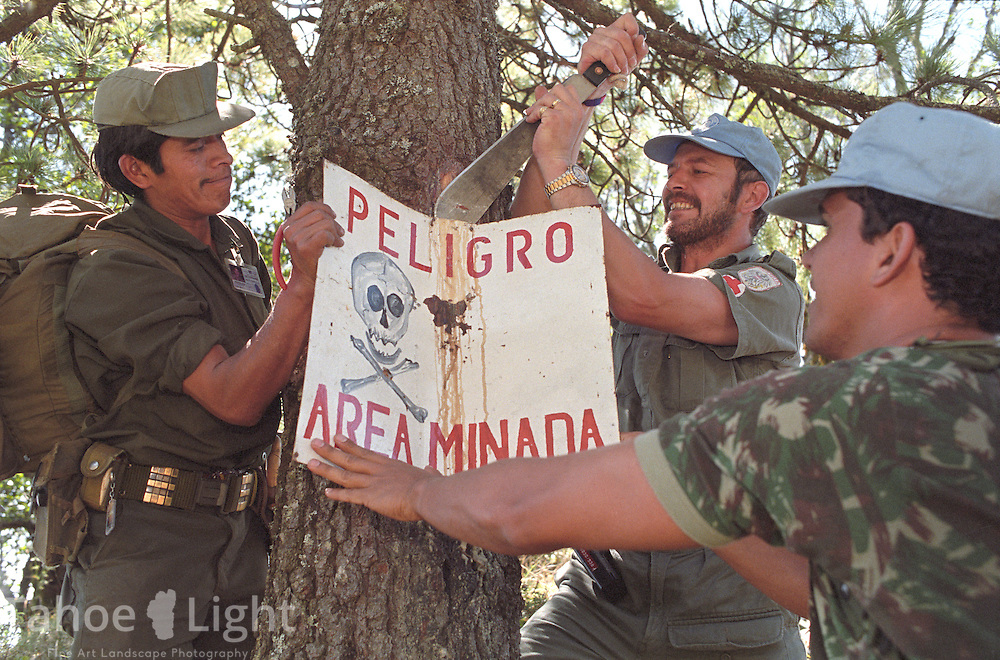 Guatemalan URNG rebel troops and united nations peace keepers remove a sign warning of a mine field after a 3 day demining operation was completed as part of the peace accords.