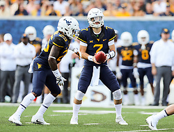 Sep 16, 2017; Morgantown, WV, USA; West Virginia Mountaineers quarterback Will Grier (7) hands the ball off to West Virginia Mountaineers running back Justin Crawford (25) during the first quarter against the Delaware State Hornets at Milan Puskar Stadium. Mandatory Credit: Ben Queen-USA TODAY Sports