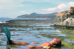 Sexy Man with flippers  relaxing in a tide pool in Hawaii
