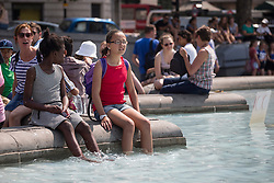 © licensed to London News Pictures. London, UK 17/07/2013. People enjoying the sunshine and hot weather in Trafalgar Square, London on Wednesday, 17 July 2013. Photo credit: Tolga Akmen/LNP