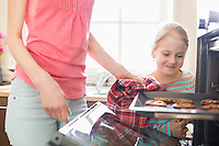 Smiling looking at mother removing cookie tray from oven at home