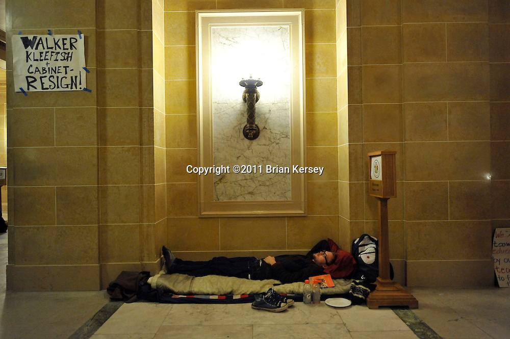 Protester Jacob Moe rests at the state capitol in Madison, Wisconsin on February 23, 2011. Twenty- four hour demonstrations have been taking place for nearly two weeks as the legislature considers the budget proposed by Republican Gov. Scott Walker, which  includes cuts in benefits for state workers and takes away many of their collective bargaining rights.    (Photo by Brian Kersey)