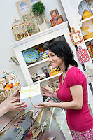 Happy woman taking box from caterer in cake shop