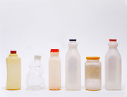 A row of various empty plastic bottles.