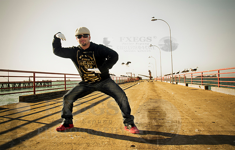 A rapper poses on a lonely dock