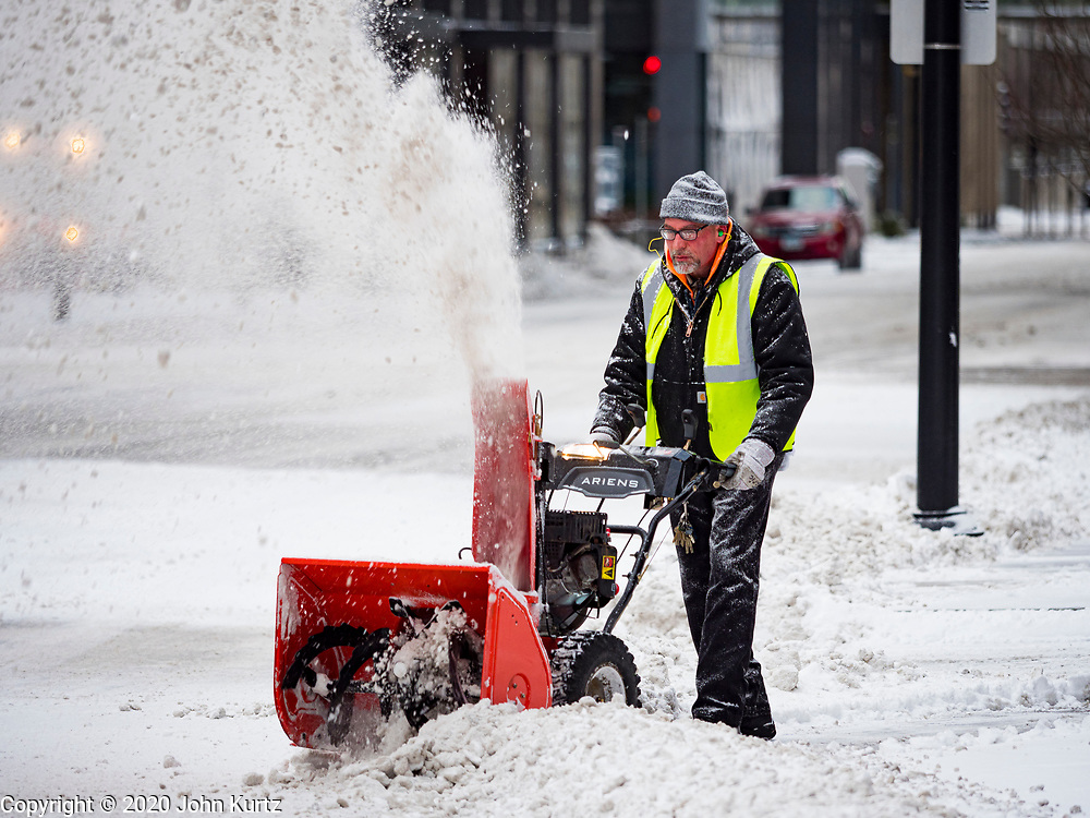 11 JANUARY 2020 - DES MOINES, IOWA:  A worker uses a snowblower to clear snow from exit of a parking garage in downtown Des Moines Saturday morning. The first significant snow in two months blanketed Des Moines Friday evening into Saturday morning. Meteorologists predicted up to six inches of snow overnight but by Saturday morning only about 3 inches had fallen in central Des Moines.      PHOTO BY JACK KURTZ