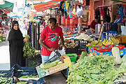 Muslim woman customer at the famous Ballero street market for vegetables and other fresh food in Palermo, Sicily, Italy