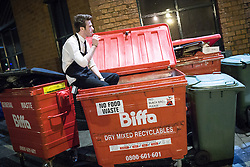© Licensed to London News Pictures . FILE PICTURE DATED 05/05/2013 of a night time worker sitting in a wheelie bin smoking a cigarette overnight , as the British Home Secretary , Theresa May , takes questions at the annual Police Federation conference on licensing and policing the night time economy , today (Wednesday 15th May 2013) . Photo credit : Joel Goodman/LNP
