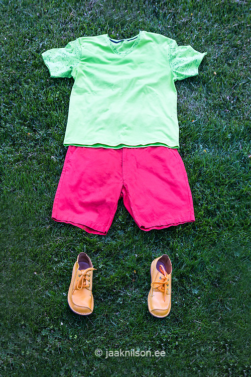 Men`s summer casual clothes and shoes lying in grass. Figure.