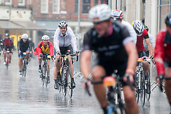 © Licensed to London News Pictures. 10/08/2014. Kingston, UK. The riders pass throughout the centre of Kingston.  Cycling enthusiasts of all ages take part in the Prudential RideLondon cycling event through Kingston Upon Thames, Surrey in heavy rain today 10th August 2014. RideLondon is an annual two-day festival of cycling and part of the legacy of the 2012 Olympic Games. Photo credit : Stephen Simpson/LNP